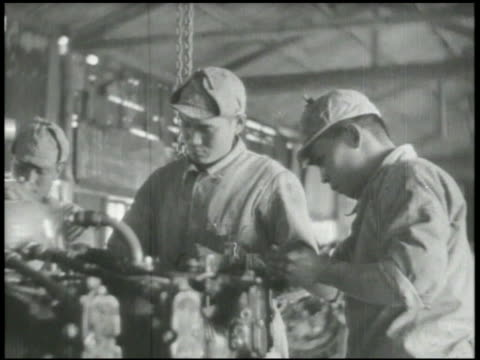 Japanese engineers repairing fighter aircraft engine part in factory stamping airplane machine gun ammunition disassembling engine part from fighter...
