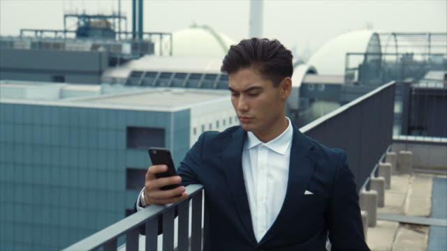 vídeos de stock, filmes e b-roll de japonês empreendedor usando um smartphone (câmera lenta) - extremo oriente