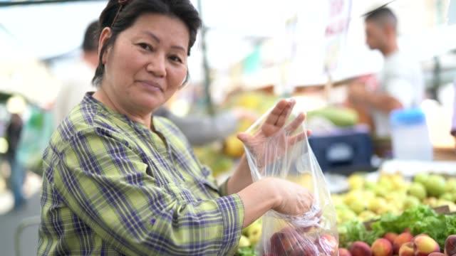vídeos de stock, filmes e b-roll de mulher de etnia japonesa comprando frutas no mercado dos fazendeiros - orgânico