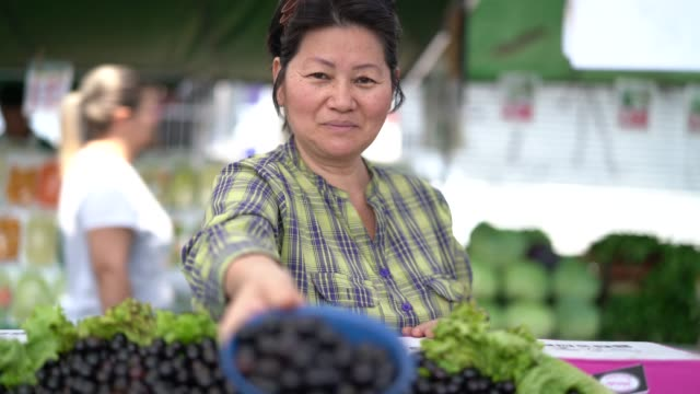 日本民族女性 jabuticaba を購入/ファーマーズ ・ マーケットの jaboticaba - ファーマーズマーケット点の映像素材/bロール