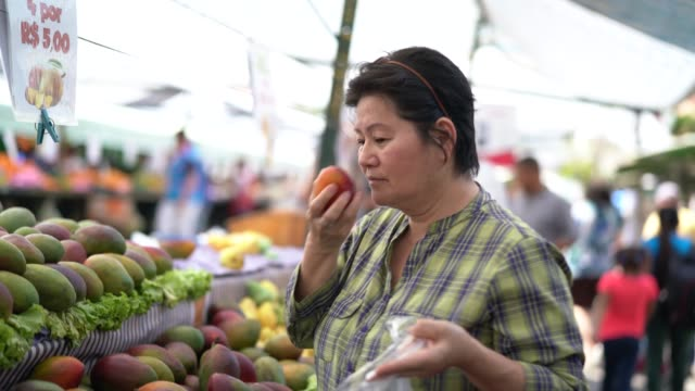 japanese ethnicity woman buying mango on farmers market - agricultural fair stock videos & royalty-free footage