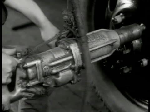 stockvideo's en b-roll-footage met japanese factory worker. pneumatic control on wheel bolts. factory worker tightening wheel bolts on truck assembly line. worker. - 1949