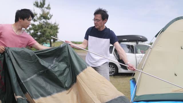 キャンプにテントを設置する日本の家族 - パート2/5 - 両親点の映像素材/bロール