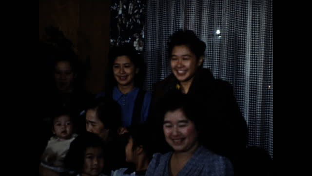 japanese family gathered around white clothed table having christmas dinner; woman in blue dress cutting cake; men holding babies and children eating... - 1930 1939 stock videos & royalty-free footage
