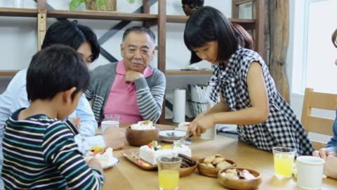 vídeos y material grabado en eventos de stock de familia japonesa con torta en casa - mesa de comedor