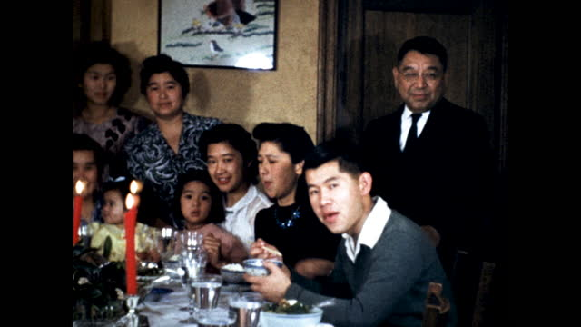 japanese family having christmas dinner, men in suits, children waves at the camera; japanese painting in the background - 1930 1939 stock videos & royalty-free footage
