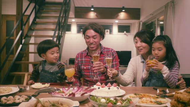 vídeos de stock e filmes b-roll de japanese family makes a celebratory toast during christmas dinner - japão