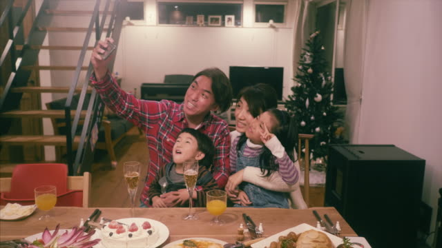 japanese family makes a selfie during christmas dinner - family with two children stock videos & royalty-free footage