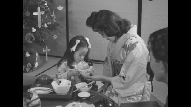 Japanese family sits on floor around table eating with a Christmas tree and CARE package behind them / woman helps ægirl both dressed in kimonos use...