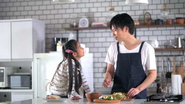 台所で話す日本人の父と娘 - 食べ物点の映像素材/bロール