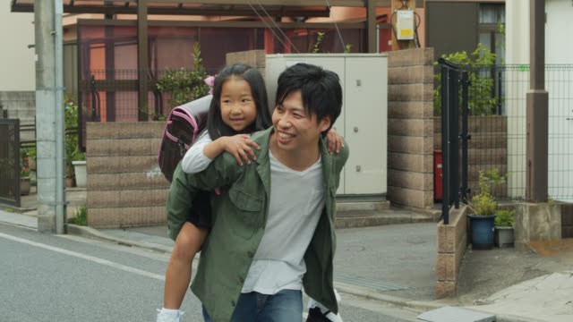 japanese father carrying daughter on back - uniform stock videos & royalty-free footage