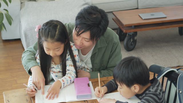 japanese father helping daughter to trace kanji - quaderno video stock e b–roll