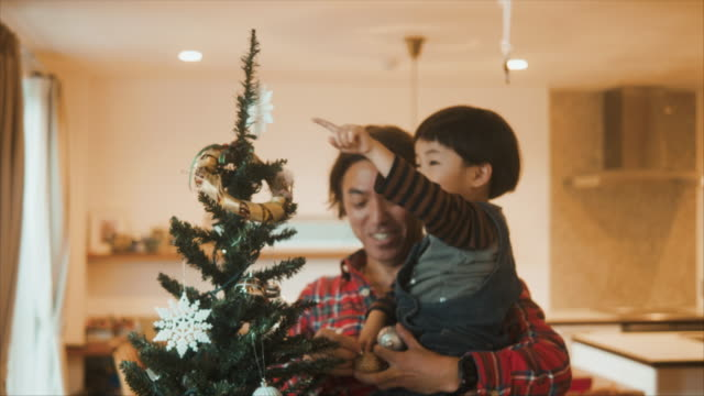Japanese father is decorating christmas tree with his children