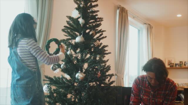 日本の父は子供たちと一緒にクリスマスツリーを飾っている - クリスマスの飾り点の映像素材/bロール