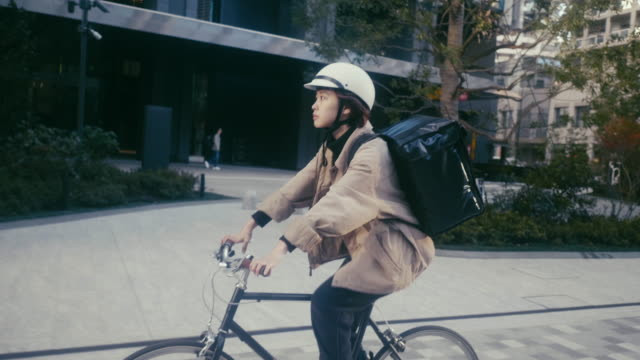 japanese female food courier delivering orders in tokyo (slow motion) - helmet stock videos & royalty-free footage