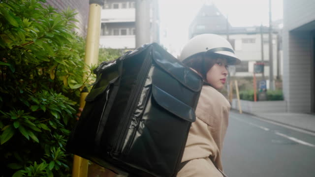 東京で注文を届ける日本の女性食宅配業者(スローモーション) - 配達点の映像素材/bロール