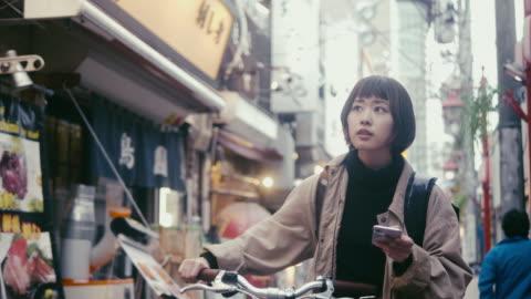 東京で納品先住所を探している日本女性食宅配業者(スローモーション) - 路地点の映像素材/bロール
