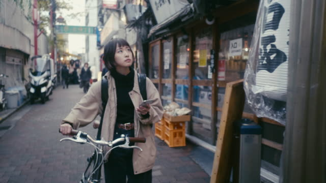 japanese female food courier looking for the delivery address in tokyo - looking around stock videos & royalty-free footage