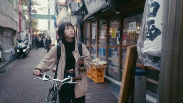 vidéos et rushes de courrier alimentaire féminin japonais recherchant l'adresse de livraison à tokyo - regarder autour de soi
