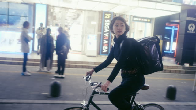 japanese female food courier looking for the delivery address in tokyo (slow motion) - tracking shot stock videos & royalty-free footage