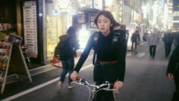 Japanese female food courier looking for the delivery address in Tokyo (slow motion)