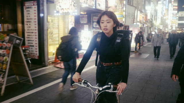 japanese female food courier looking for the delivery address in tokyo (slow motion) - 20 24 years stock videos & royalty-free footage