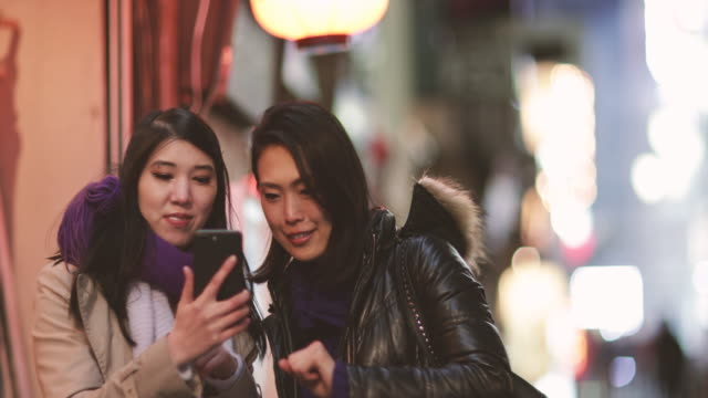 japanese female friends looking at smart phone in shinjuku at night, tokyo, japan - only japanese stock videos & royalty-free footage