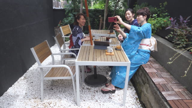 japanese female friends taking selfie picture at outdoor cafe - yukata robe stock videos & royalty-free footage