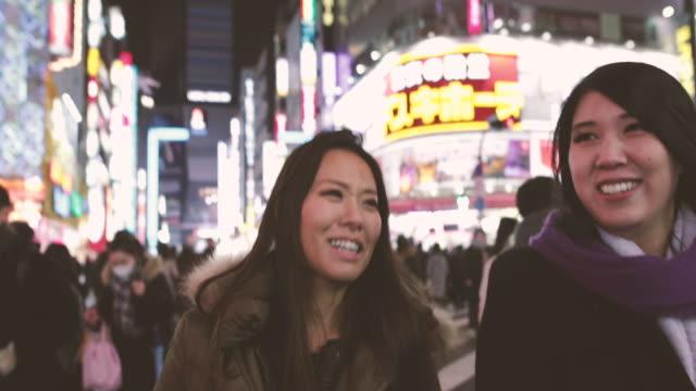 Japanese female friends walking on street in Shinjuku at night, Tokyo, Japan