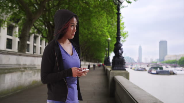 japanese female in black hoodie texting on mobile phone by river thames - schwarzes hemd stock-videos und b-roll-filmmaterial