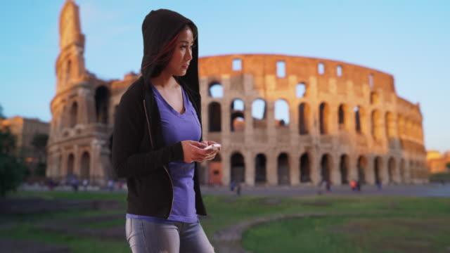 japanese female in black hoodie texting on mobile phone near colosseum - schwarzes hemd stock-videos und b-roll-filmmaterial