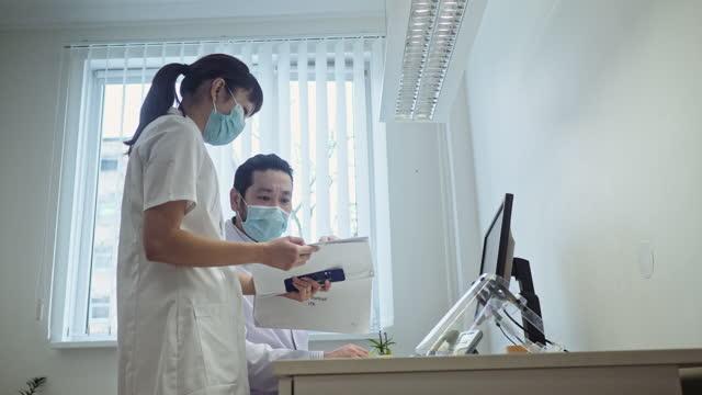 vídeos y material grabado en eventos de stock de enfermera japonesa y doctora masculina discutiendo trabajo detrás de la pantalla de la computadora - unidad de entrada