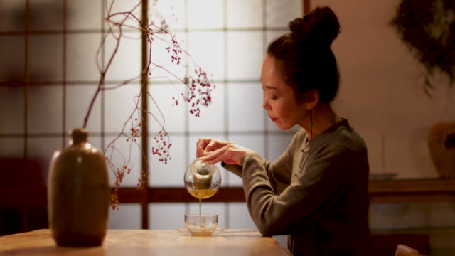 Japanese Female pouring green tea in traditional house, Kyoto, Japan