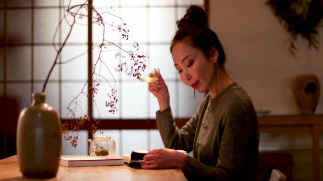 vídeos y material grabado en eventos de stock de japanese female reading book at home and drinking tea, kyoto japan - sado