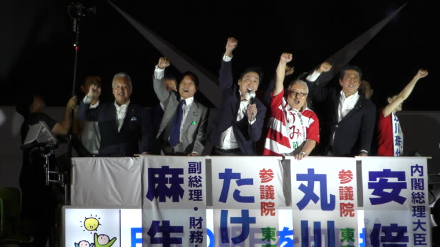 japanese finance minister taro aso prime minister shinzo abe candidates keizo takemi and tamayo marukawa raise their fists during a campaign event... - akihabara station stock videos and b-roll footage