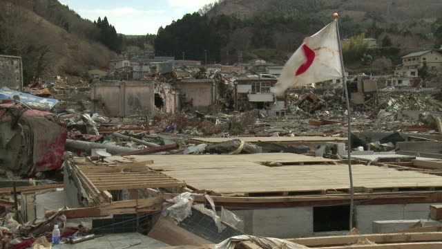 japanese flag flying in onagawa town in in oshika district, miyagi, japan on 3rd april 2011, 3 weeks after a tsunami hit north east japan, caused by magnitude 9 tohoku. - tsunami stock videos & royalty-free footage