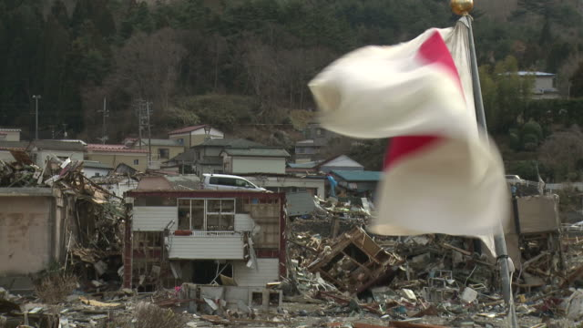 vidéos et rushes de japanese flag flying in onagawa town in in oshika district, miyagi, japan on 3rd april 2011, 3 weeks after a tsunami hit north east japan, caused by magnitude 9 tohoku. - patriotism