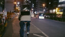 Japanese food courier cycling in the night (slow motion)