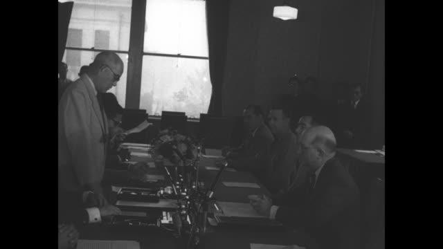 Japanese Foreign Minister Katsuo Okazaki sits down at table during Tokyo meeting / US Ambassador to Japan John Moore Allison takes seat at table /...