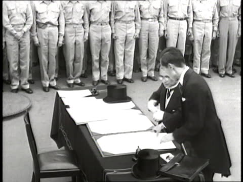 Japanese Foreign Minister Mamoru Shigemitsu sits down and signs a surrender document during World War II