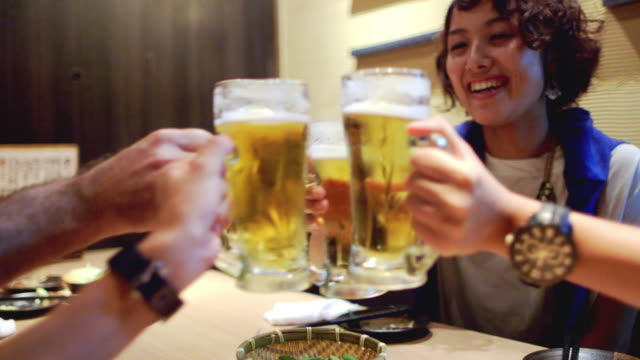 vídeos de stock e filmes b-roll de ms japanese friends raise beer glasses in a toast / tokyo, japan - beer alcohol