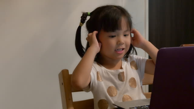 Japanese Girl aged 4 years using laptop for online English lesson