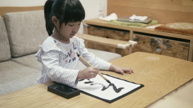 japanische mädchen tun japanische kalligraphie am neujahrstag - kalligraphieren stock-videos und b-roll-filmmaterial