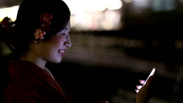 Japanese Girl in a Kimono Texting at night in Shibuya