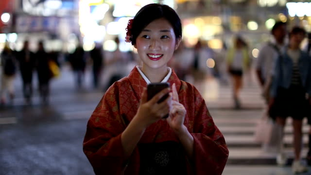 Japanese Girl in a Kimono Texting at the Shibuya Crossing