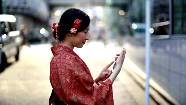 japanese girl in a kimono texting in shibuya - kimono stock videos and b-roll footage