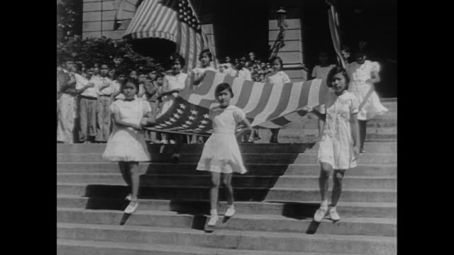 japanese girls carry a large american flag as they walk passed crowds of children with their hands over their hearts in the us during wwii - guerra del pacifico video stock e b–roll
