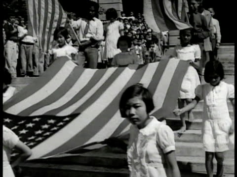 japanese girls carrying unfurled u.s. flag down steps. children w/ hands clasped over heart. children bringing flag down steps, celebration. vs... - pacific islanders stock videos & royalty-free footage