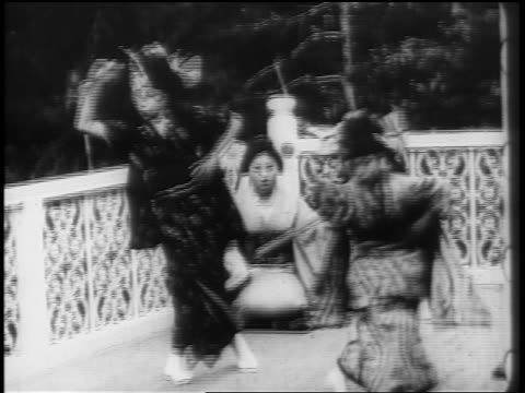 B/W 1898 2 Japanese girls in traditional clothing dancing as woman in background plays shamisen / newsreel