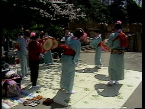 japan tokyo la cherry blossom on trees as music plays sof tilt down girls in traditional costume dancing in circle ms girls dancing waving hats cms... - 科学技術点の映像素材/bロール